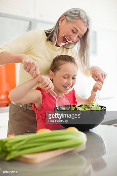 Abuela y granddaughter preparar una ensalada juntos