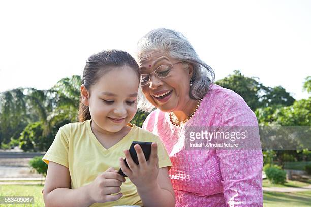 Grandmother and granddaughter reading an sms