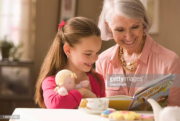 Grandmother and granddaughter reading book