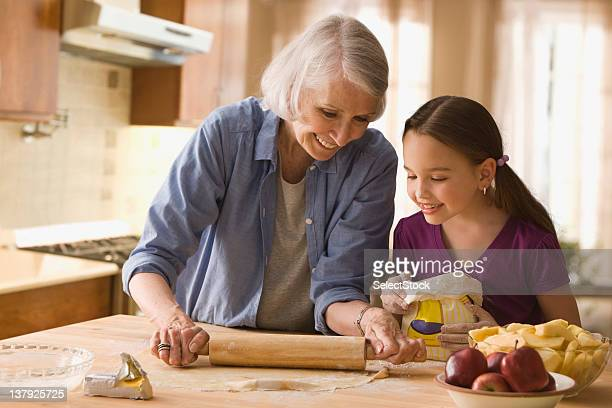 Grandmother and granddaughter rolling dough