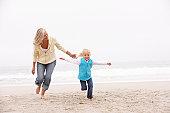 Grandmother And Granddaughter Running Along Winter Beach