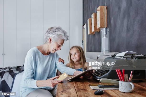 Grandmother and granddaughter shopping online at home