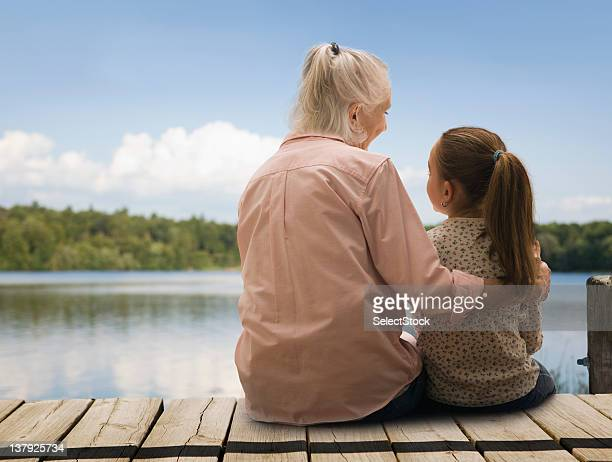 Grandmother and granddaughter sitting on the docks