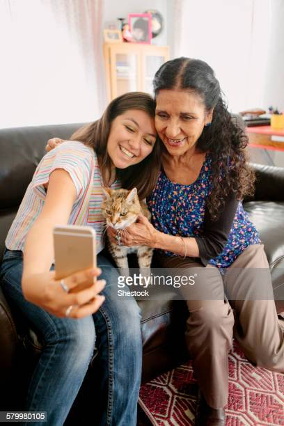 Grandmother and granddaughter taking selfie with cat on sofa