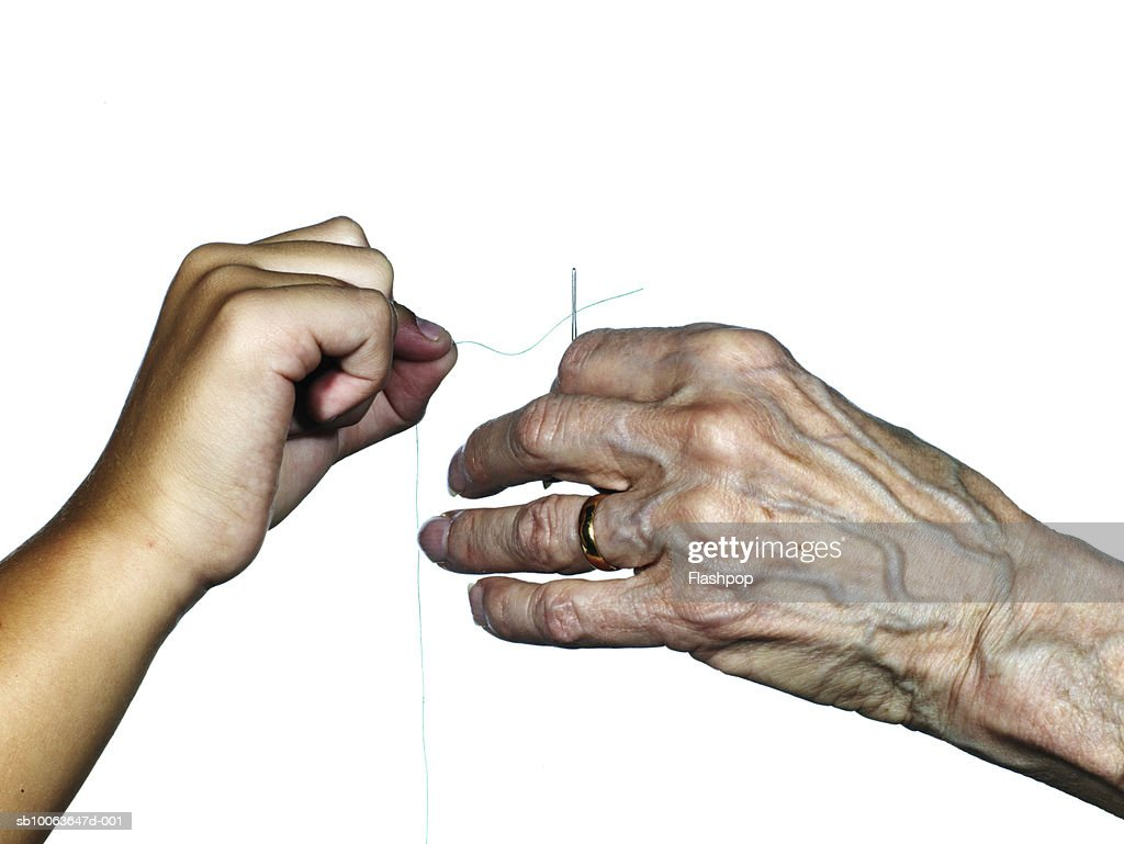 Grandmother and granddaughter (8-9) threading needle, close-up : Stock Photo