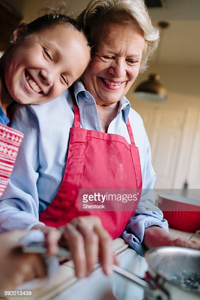 Grandmother and granddaughter using kitchen sink