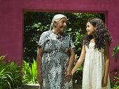 Grandmother and granddaughter walking in garden