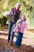 Grandmother and granddaughter walking on path outdoors smiling (selective focus)