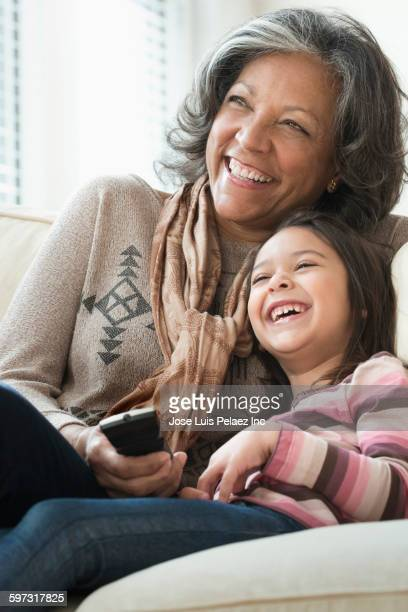 Grandmother and granddaughter watching television on sofa