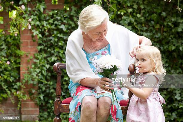 Grandmother and granddaughter with bunch of flowers at garden party