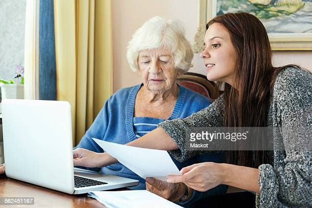 Grandmother and granddaughter with document using laptop at home