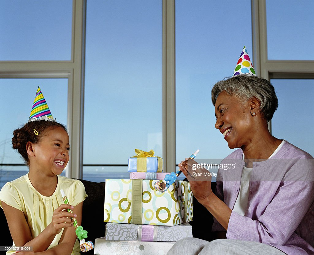 Grandmother and granddaughter (8-10) with gifts and party blowers : Stock Photo