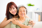 Grandmother and granddaughter. Young woman carefully takes care of old woman