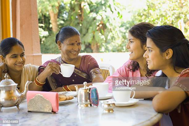 Grandmother and granddaughters sitting at table together