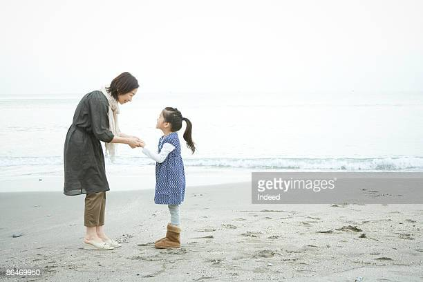 Grandmother and granddauter holding hands on beach