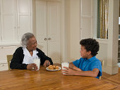 Grandmother and grandson (10-11) at table, talking