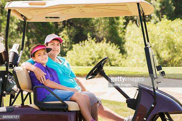 Grandmother and grandson driving golf cart on course
