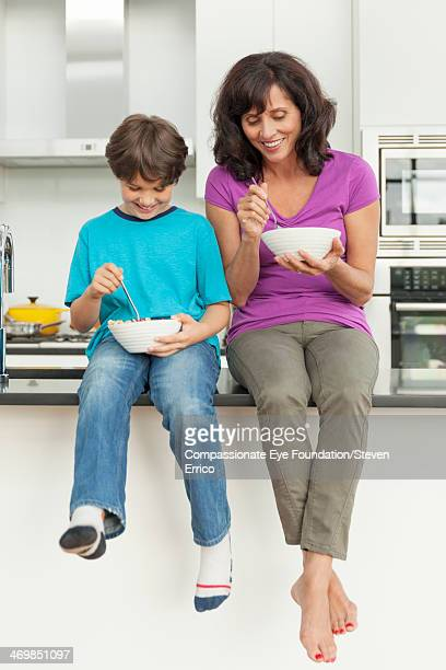 Grandmother and grandson eating bowls of cereal