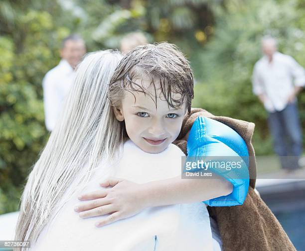 Grandmother and grandson (4-6) embracing by pool