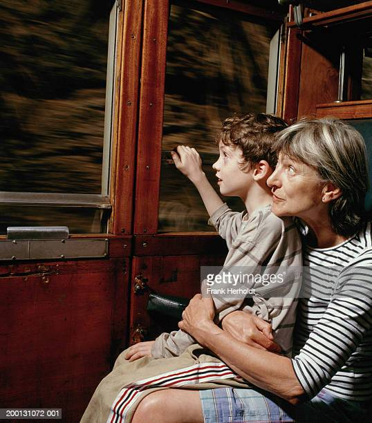 Grandmother and grandson (6-8) looking out of train window
