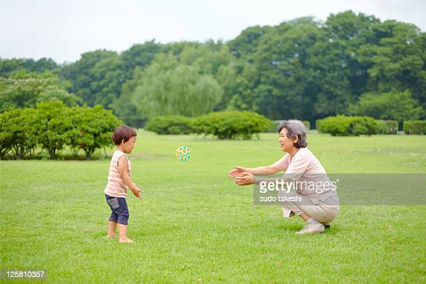 Grandmother and grandson playing with ball.