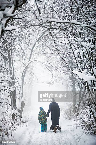 Grandmother and grandson walking with dog in snowy winter forest