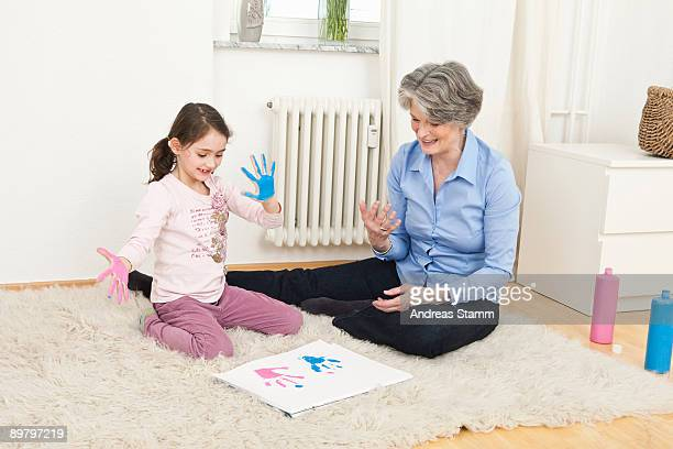 A grandmother and her granddaughter finger painting