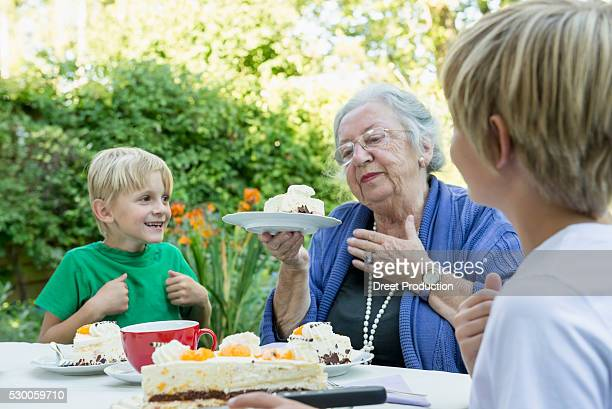 Grandmother and her two grandsons with cream cake