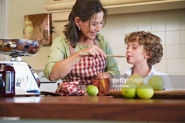 Grandmother and little boy cooking food at home
