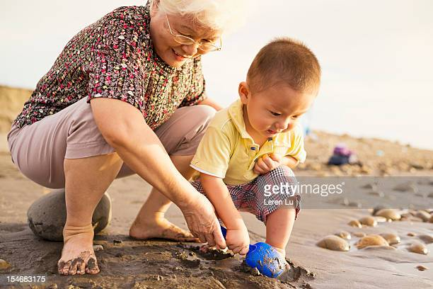 Grandmother and little boy playing on beach