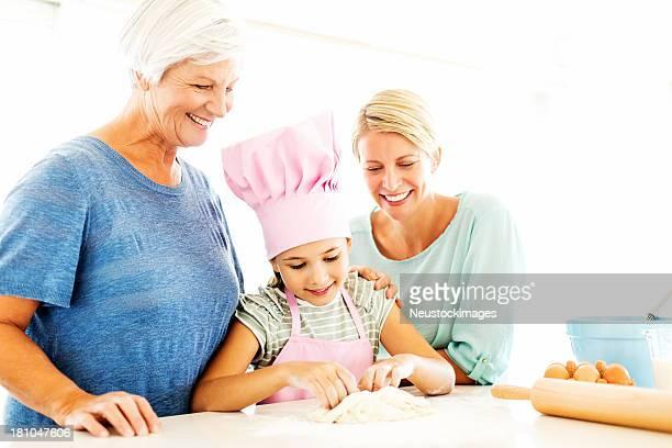 Großmutter und Mutter mit Mädchen Kneten Teig In der Küche