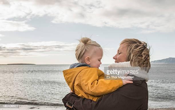 Grandmother and toddler hugging at coast