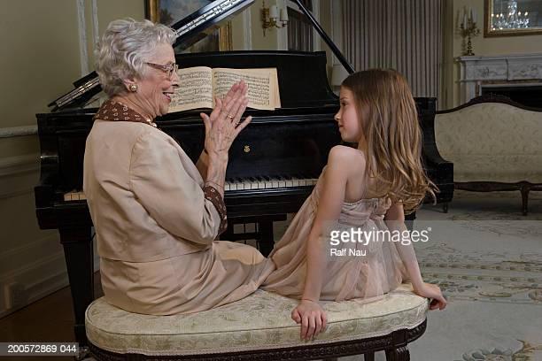 Grandmother applauding granddaughter (6-8) sitting at piano