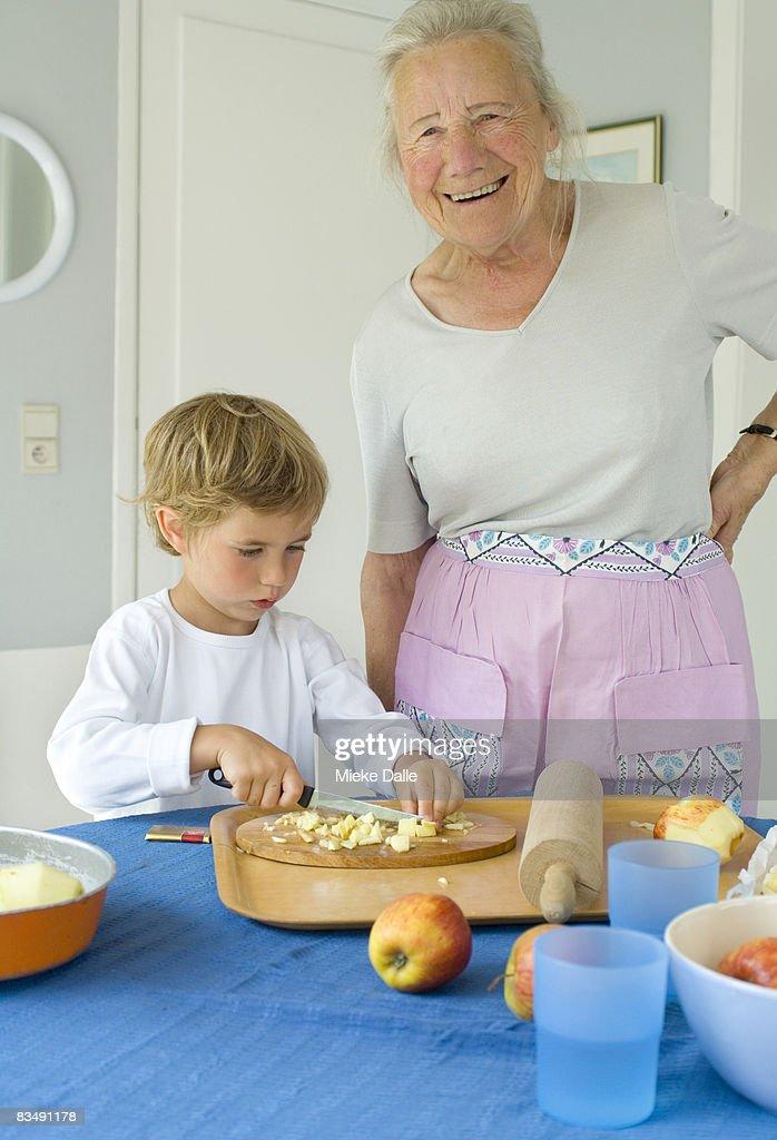 grandmother baking pie with grandchildren : Stock Photo