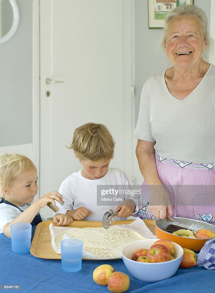 grandmother baking pie with grandchildren : Stock Photo