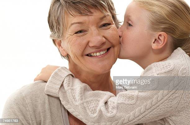 Grandmother being kissed by granddaughter (7-9), smiling