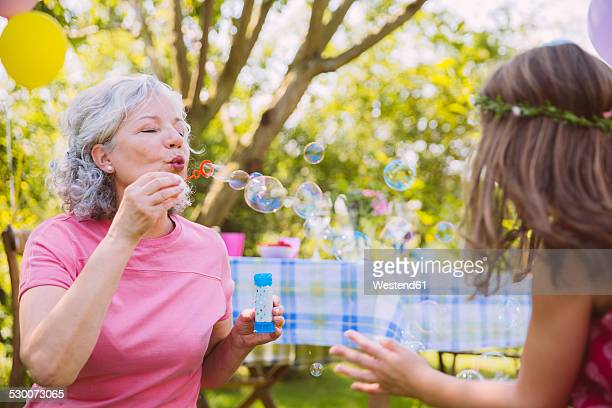 Grandmother blowing soap bubbles for girl playing in garden