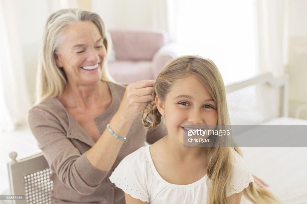 Grandmother braiding granddaughter's hair : Stock Photo