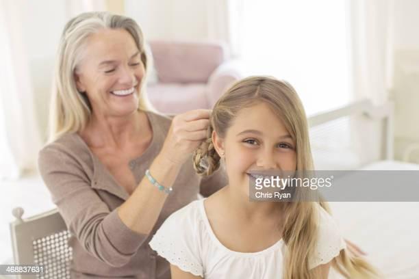 Grandmother braiding granddaughter's hair