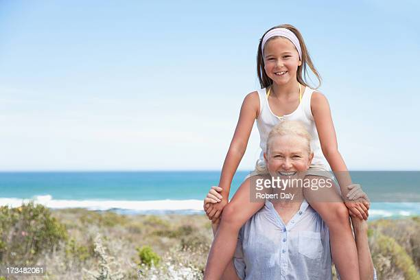 Grandmother carrying granddaughter on shoulders on beach