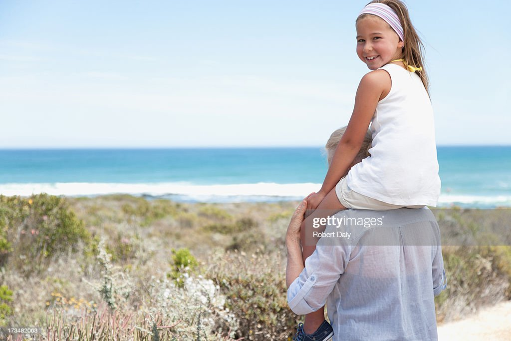 Grandmother carrying granddaughter on shoulders on beach : Stock Photo