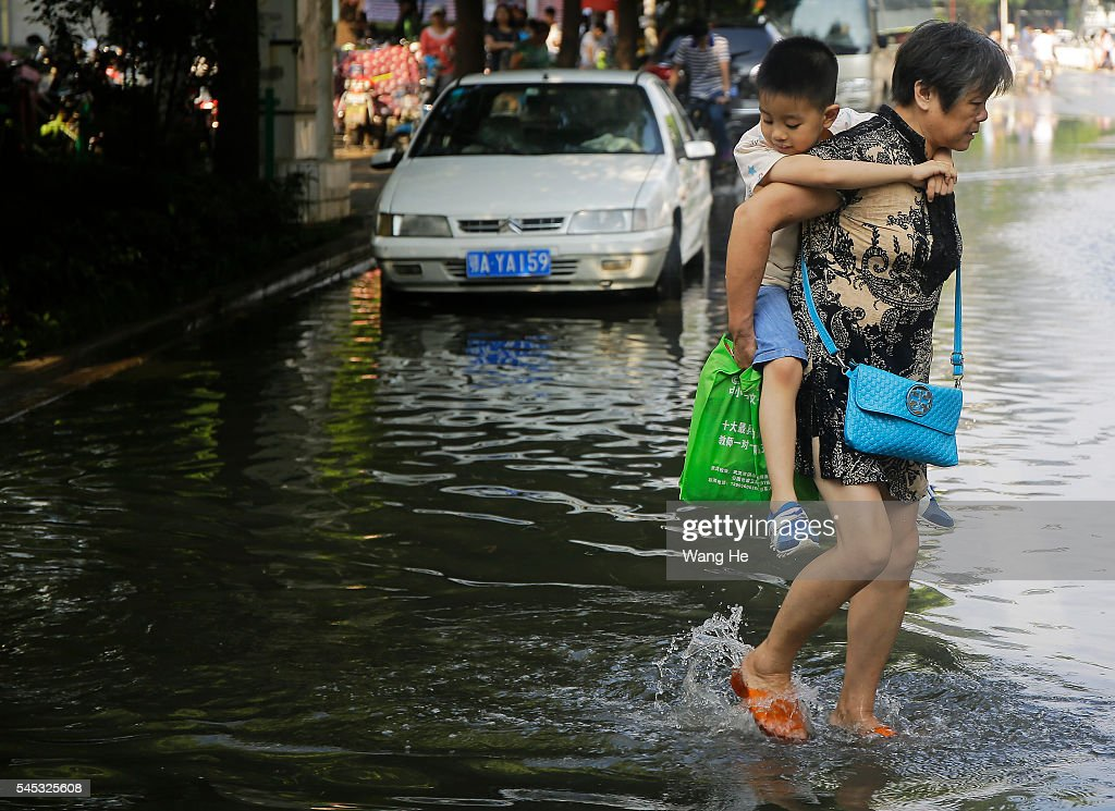 Grandmother carrying grandson walk on a flooded street in South Lake Community of Wuhan Hubei Province of China on 7th July 2016
