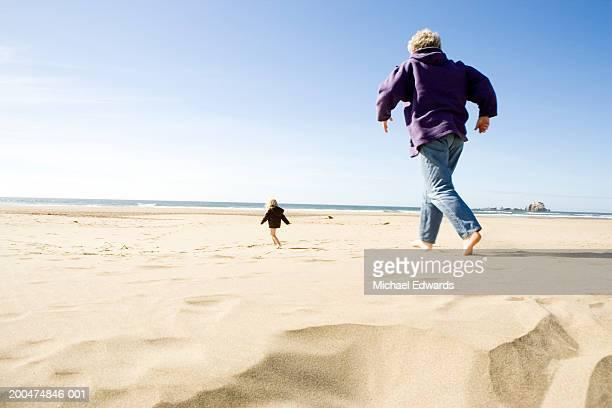 Grandmother chasing granddaughter (2-4) on beach
