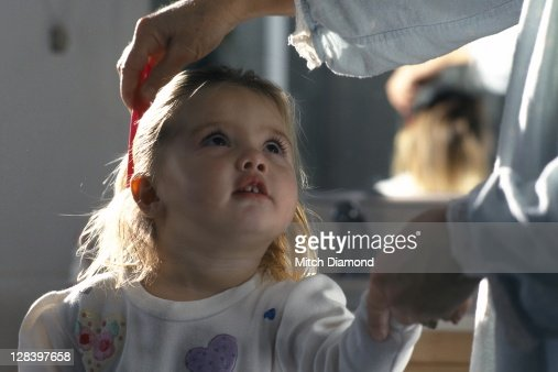 Grandmother combing granddaughters hair : Stock Photo
