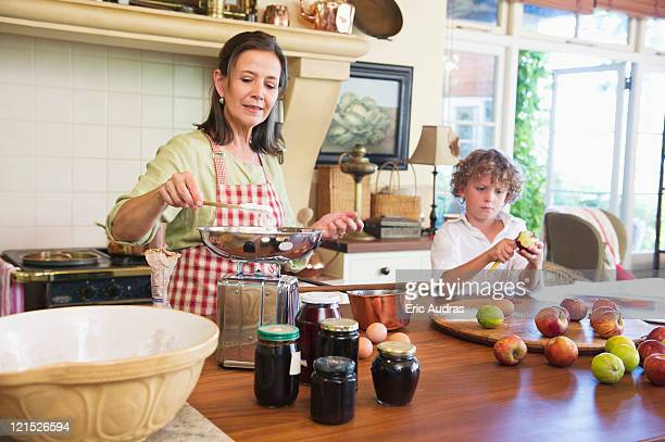 Grandmother cooking food and little boy peeling an apple at home