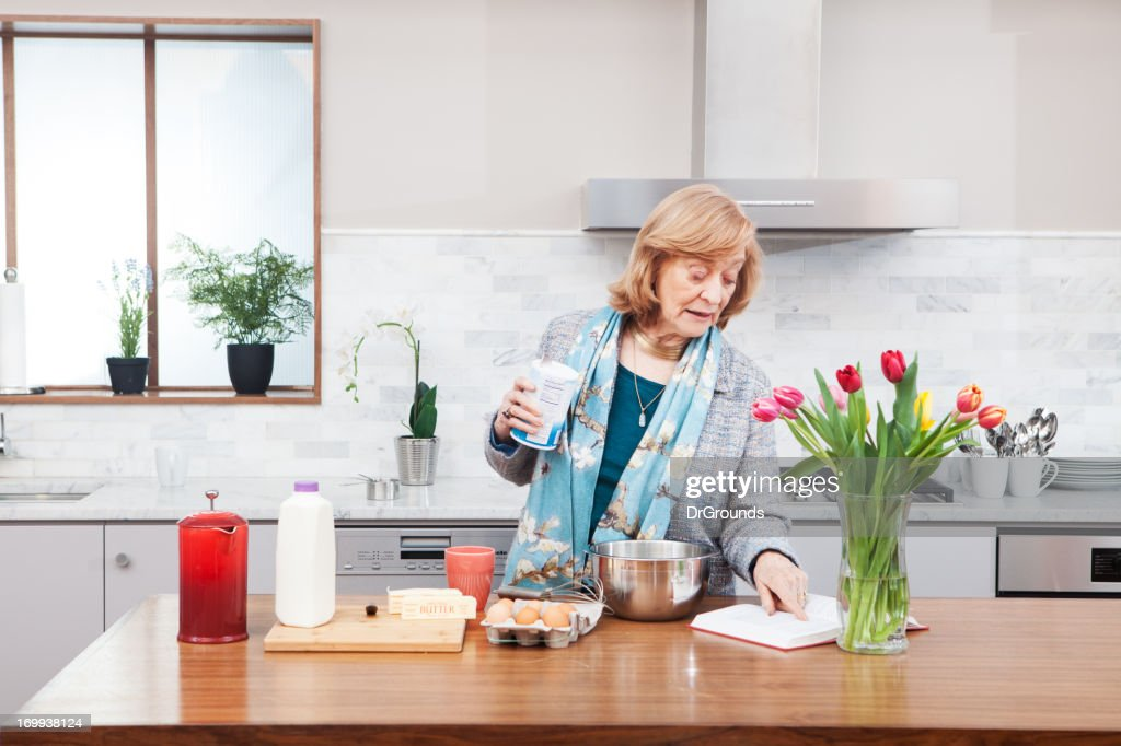 Grandmother cooking her special recipe in kitchen : Stock Photo