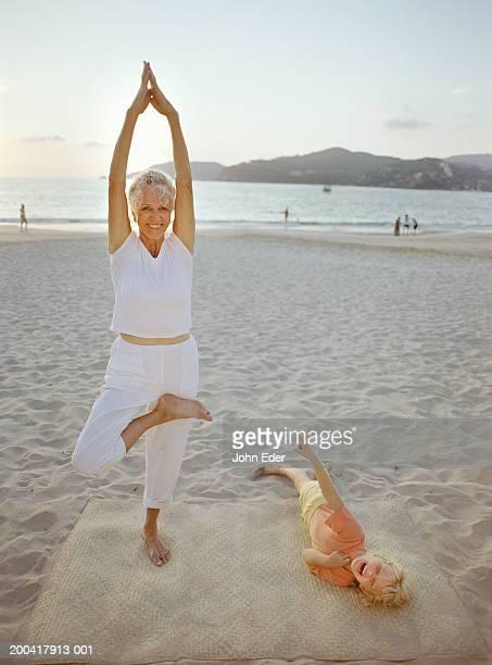 Grandmother doing yoga on beach, girl (5-7) laughing