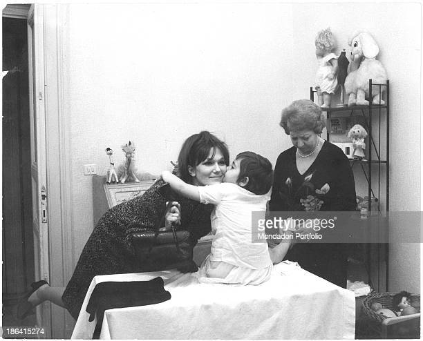 Grandmother dressing a children hugging and kissing his working mother because she's ready to go out The parents live in the home belonging to...
