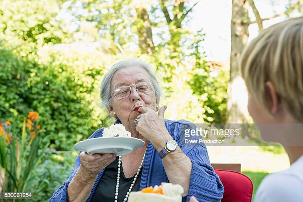 Grandmother eating cream cake with her grandson