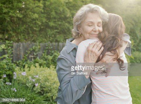 Grandmother embracing adult granddaughter